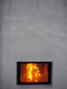 Kamin in einer Sichtbetonwand.